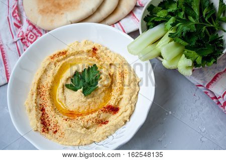 Home classic hummus with celery pitoy.Vid top on gray concrete background. Vegan Food Concept.