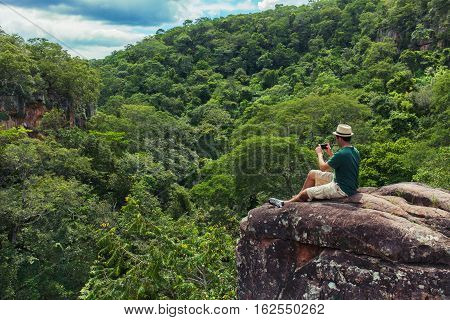 Young man tourist sittig on the rock at the top of mountain and taking photo with smartphone of a green tropical valley. 25-30 years old with t-shirt, shorts and hat.