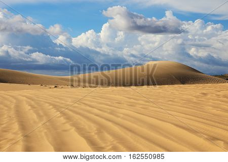 White sand dunes on the background of blue sky with clouds near Mui Ne place Vietnam