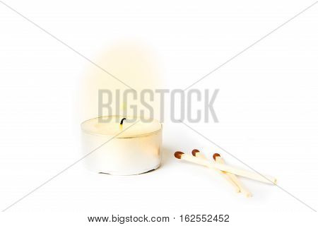 Lit tea candle with matches on white background