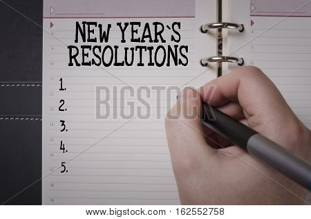 Woman hand writing New Year`s Resolutions. New Year's Resolution concept