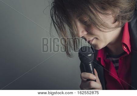 Close-up of a woman singing into the dynamic microphone in the dark