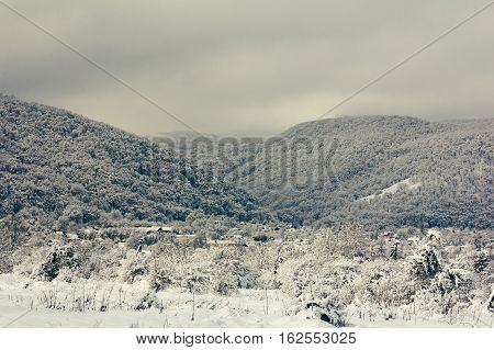 winter landscape a village in the foothills of snowy hills cloudy early in the morning