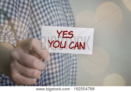 Man showing Yes You Can card. Blurred bokeh background.