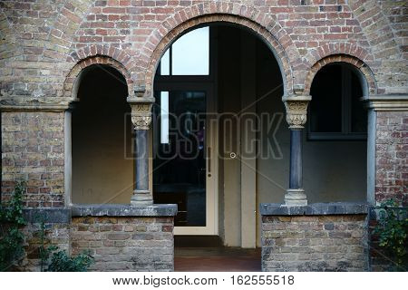 The arched side entrance of a church with columns.