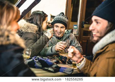 Happy friends drinking beer and eating chips by night - Friendship concept with cheerful people having fun at bar restaurant resort with snow equipment - High iso image with shallow depth of field