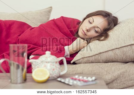 Sick woman covered with a blanket lying in bed with high fever and a flu resting. Teapot pills and lemon on the table