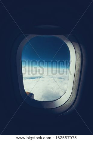 View through airplane porthole of horizon clouds and dark sky