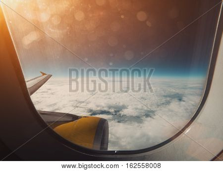 Beautiful wide view from window of aircraft: cloudscape horizon airplane wing and orange engine flare and stylish lens dirt