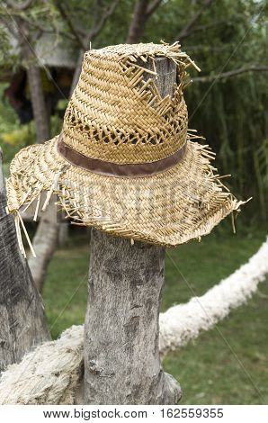 Old tattered straw hat hung on a stake closeup