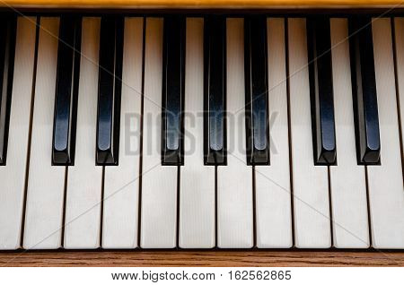 Old grunge piano keyboard. One octave. Top view of piano. Musical instrument indoors. Inspiration background.