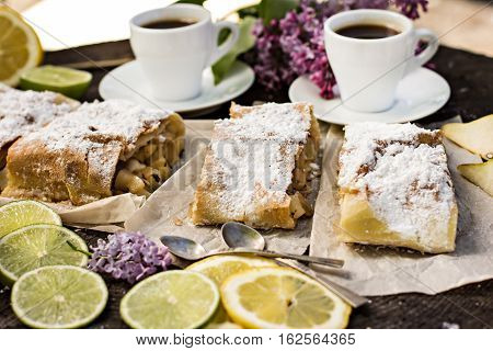 pie strudel with pear and lemon. Cup of coffee. Picnic Breakfast in nature. Food in nature.