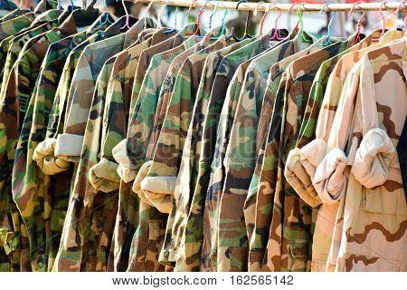 Many military shirt hang on a wood clothesline