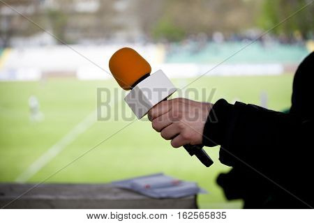 hand hold microphone for interview during a football mach