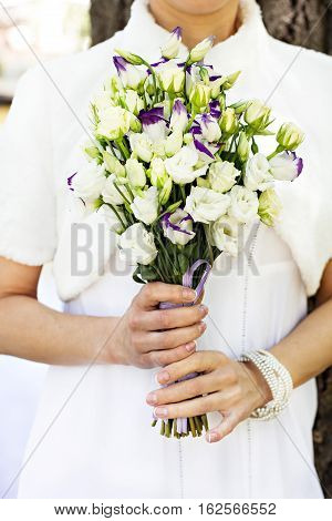 the bride's bouquet. white and purple flowers.The bride holds the wedding bouquet.