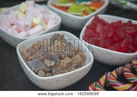 Many Different Sweets Are In White Bowls.