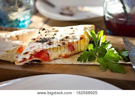 roll pita with cheese and tomatoes on the table