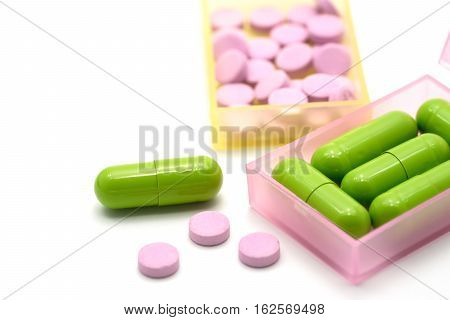 Medical pills capsule in pill box on white background.