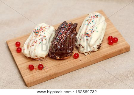 Three eclair cakes with white and brown cream on wooden board