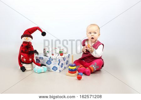 Christmas, X-mas, Holidays, Children concept. Studio shot of adorable baby girl in red dress opening Christmas presents.