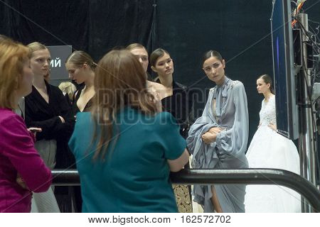 Moscow, Russia - October 19, 2016: Backstage of Moscow fashion week. Models in sexy dresses looking to monitor for runway show.