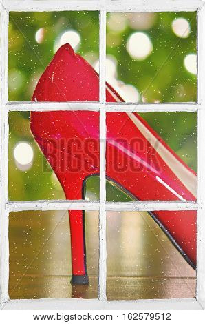 red high heel shoe with bokeh Christmas lights in windowpane with snowflakes