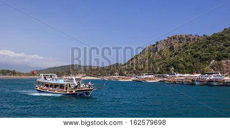 Kekova, Antalya, Turkey - April 26, 2014: Bay near Kekova, which is an ancient Lycian region in Antalya. In the foreground, a pleasure boat with tourists, in the background - a marina with pleasure craft.