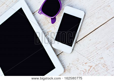 Tablet computer mobile phone and sunglasses on a wooden table
