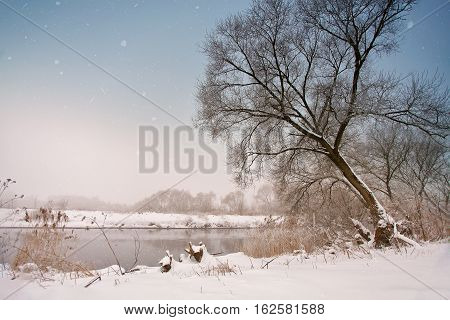 Snowfall Over The River. Winter Misty Cloudy Snowy Weather.