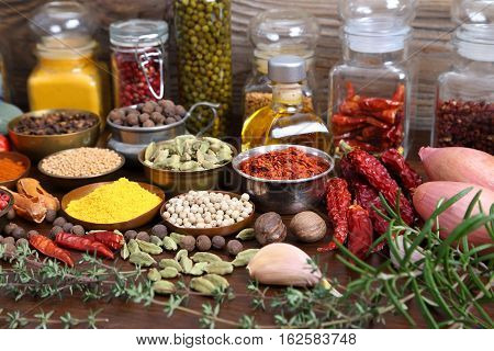 Flavorful colorful spices in metal bowls and glass bottles on wooden background.