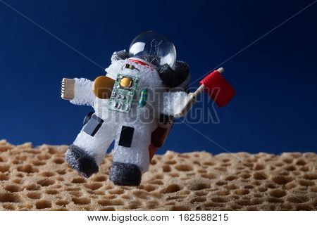 Spaceman floating stratosphere, fantastic planet landscape. blue sky background. Light bulb character dressed in spacesuit astronaut ammunition. Flying cosmonaut red flag.