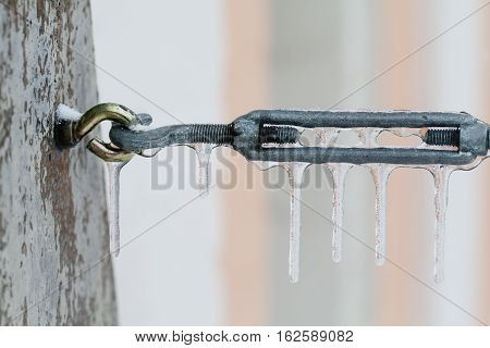 Frozen metal connector with icicles. Winter season cold weather background. macro view soft focus shallow depth of field