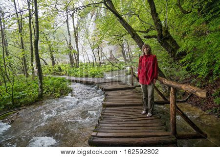 Woman dressed in red windbreaker situated on wood bridge under stream. Green spring trees in background. Place - Plitvice Lakes National Park.