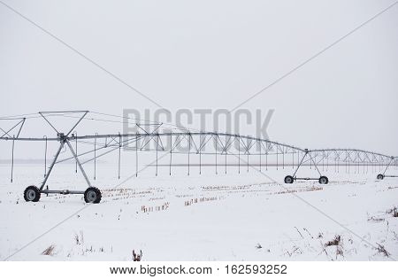 An agricultural metal irrigation system on wheels in a rural winter landscape