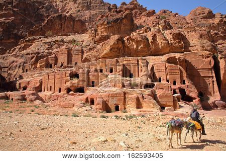 PETRA, JORDAN : The Street of Facades with a Bedouin man riding his donkeys in the foreground