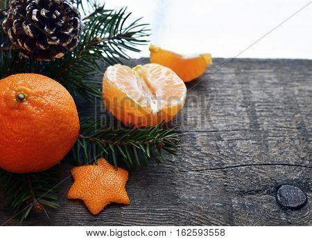 Christmas decoration.Tangerines with fir tree branch and pine cone on wooden rustic table.Mandarin oranges fruits.Soft focus.Selective focus.Copy space.