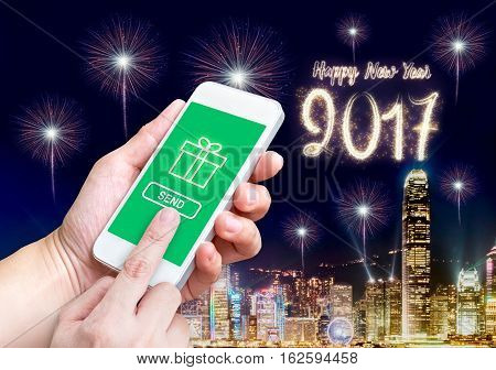 Hand holding mobile and send online gift with night cityscape building and happy new year 2017 firework at backgroundModern lifestyle celebration.
