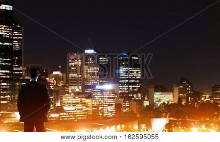 Elegant businessman in a suit looking at night city