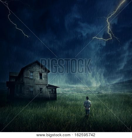 Spooky landscape as a young boy walking in the meadow look at a ghost haunted house below a dark stormy sky.