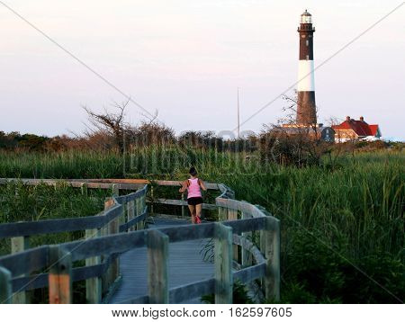 A runner jogs on the boardwalk at The Fire Island Lighthouse