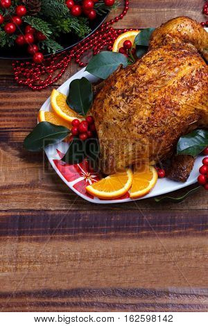 Roasted whole chicken with Christmas decoration. Wooden background.Top view