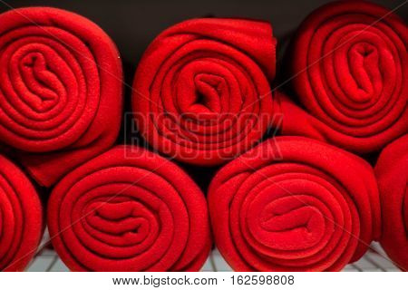 Rolls of many red plaids stand on the shelf