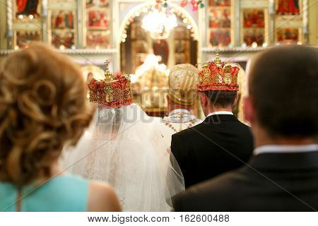 Bride and fiance stand in crowns in the front of church altar