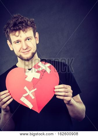 Healed love. Valentines Day concept. Young happy man holding big red heart with plaster. Boyfriend healing relationship.