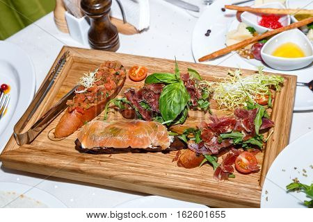 appetizers of seafood and meat on wooden plate in restaurant