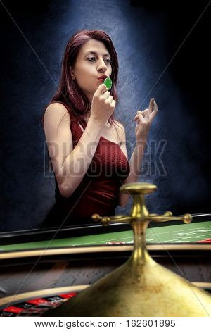 gambler woman bet on roulette table at casino