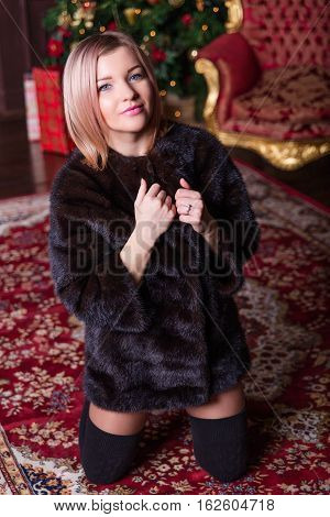 Blonde Girl Posing In A Fur Coat Near The Christmas Tree