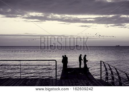 Fishermen on pier. Silhouettes of people on early sunny morning in backlight. Fishing in sea at sunrise. Flocks of migrating birds over water. Ships on horizon. Toned black and white color processing. Nice soft warm light