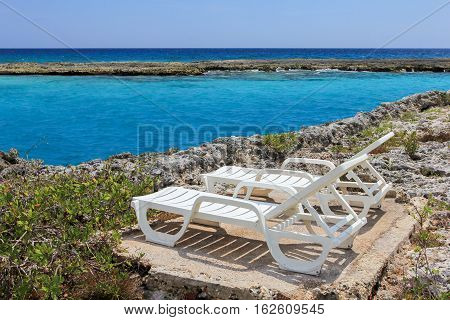 two chaise-lounges on the coral beach of the Caribbean sea