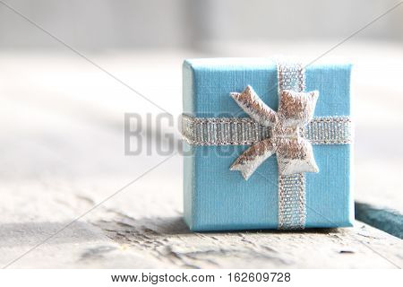 Blue Gift box with ribbon on vintage wooden background